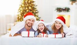 愉快的家庭母亲父亲和孩子在圣诞节早晨在床上 免版税图库摄影