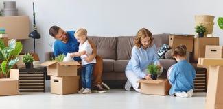 愉快的家庭母亲父亲和孩子移动向新的公寓 免版税库存照片
