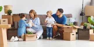 愉快的家庭母亲父亲和孩子移动向新的公寓 免版税库存图片