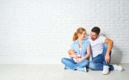 愉快的家庭母亲,一个新出生的婴孩的父亲在地板上的在blan附近 库存图片