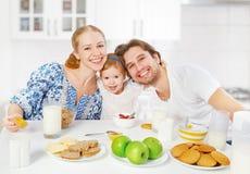 愉快的家庭母亲,父亲,儿童食用小的女儿早餐 库存图片