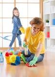愉快的家庭清洗屋子 母亲和她的儿童女儿在房子里做清洁 免版税库存照片