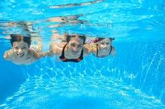 愉快的家庭游泳水下在水池 库存照片