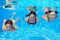 愉快的家庭游泳水下在水池 免版税库存图片
