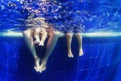 愉快的家庭游泳水下的照片在蓝色水池的 库存图片