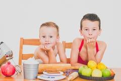 愉快的家庭滑稽的孩子准备苹果饼,在白色背景 库存图片