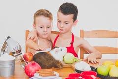 愉快的家庭滑稽的孩子准备苹果饼,在白色背景 免版税图库摄影