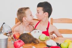 愉快的家庭滑稽的孩子准备苹果饼,在白色背景 免版税库存照片