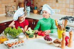 愉快的家庭滑稽的孩子在厨房里准备新鲜蔬菜沙拉 免版税图库摄影