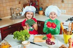 愉快的家庭滑稽的孩子在厨房里准备新鲜蔬菜沙拉 库存图片