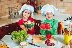愉快的家庭滑稽的孩子在厨房里准备新鲜蔬菜沙拉 库存照片