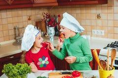 愉快的家庭滑稽的孩子在厨房里准备新鲜蔬菜沙拉 免版税库存图片