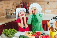 愉快的家庭滑稽的孩子在厨房里准备新鲜蔬菜沙拉 免版税库存照片