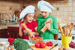 愉快的家庭滑稽的孩子在厨房里准备新鲜蔬菜沙拉 图库摄影