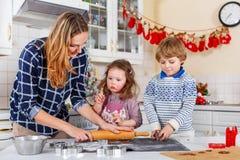 愉快的家庭烘烤圣诞节曲奇饼在家 免版税库存照片