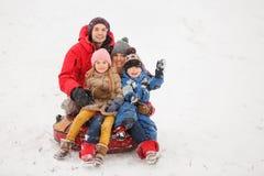 愉快的家庭照片与女儿和儿子的坐管材在冬天 图库摄影