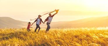 愉快的家庭父亲、母亲和儿童女儿发射风筝  库存照片
