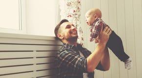 愉快的家庭父亲和儿童在家使用小的儿子 库存图片