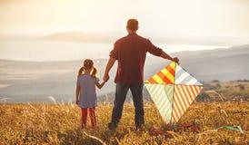 愉快的家庭父亲和儿童女儿发射在草甸的风筝 免版税库存照片