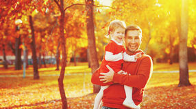 愉快的家庭父亲和儿童女儿步行的在秋天生叶 免版税库存照片