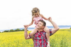 愉快的家庭父亲和儿童女儿黄色花的在自然在夏天 免版税图库摄影