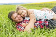 愉快的家庭父亲和儿童女儿黄色花的在自然在夏天 免版税库存图片