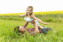 愉快的家庭父亲和儿童女儿黄色花的在自然在夏天 免版税库存照片