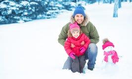 愉快的家庭父亲和儿童女孩在冬天做雪人 免版税图库摄影