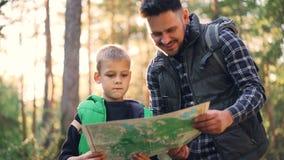 愉快的家庭父亲和逗人喜爱的儿子的慢动作看地图和谈话在远足期间在森林里在秋天 树