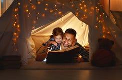 愉快的家庭父亲和读在帐篷的儿童女儿一本书 免版税库存照片