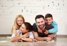 年轻愉快的家庭父母和两个孩子回家演播室 图库摄影
