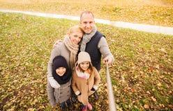 愉快的家庭用selfie棍子在秋天公园 免版税图库摄影