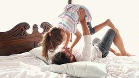 愉快的家庭田园诗小孩女儿在父亲胳膊跳,并且他们在床上落