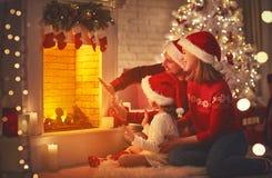 愉快的家庭由壁炉坐圣诞前夕 免版税库存图片