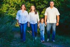 愉快的家庭由夏天的父亲朝向在公园 免版税图库摄影