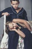 愉快的家庭男孩和女孩,兄弟在睡衣投入了床 库存图片