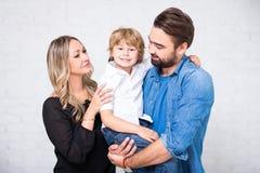 愉快的家庭画象-夫妇和小儿子在白色 免版税图库摄影