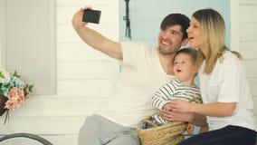 愉快的家庭的父亲做与他的妻子和小儿子的selfie前面的他们的家庭门 股票录像