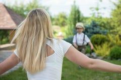 愉快的家庭的生活片刻!一起使用母亲和儿子的孩子获得乐趣在草在晴朗的夏日 免版税图库摄影