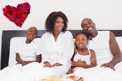 愉快的家庭的综合图象吃早餐在床 库存图片
