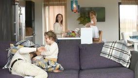 愉快的家庭获得与孩子的乐趣在舒适客厅 影视素材