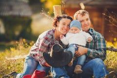 年轻愉快的家庭获得乐趣在乡下 免版税库存图片