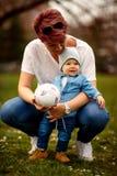 愉快的家庭获得乐趣在公园 母亲和她的一点儿子戏剧 图库摄影