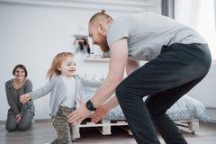 愉快的家庭获得乐趣在家 母亲、父亲和小女儿有长毛绒玩具的享用一起是 免版税库存图片