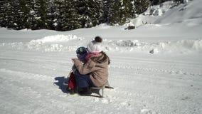 愉快的家庭获得使用的乐趣在山的一个多雪的森林在冬天 妈妈和她的两个孩子sledding 影视素材