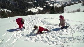 愉快的家庭获得使用的乐趣在山的一个多雪的森林在冬天 妈妈和她的两儿童投掷雪球 股票录像