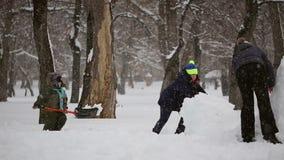 愉快的家庭雕刻雪人在雪外面 股票视频