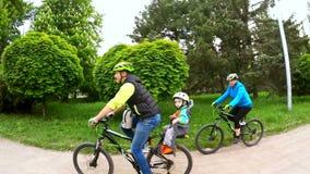 愉快的家庭骑马自行车在绿园区域 股票视频
