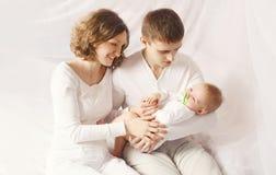 愉快的家庭,有婴孩的年轻父母画象在家 免版税库存照片