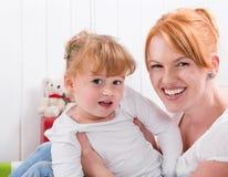 愉快的家庭:微笑对照相机- strawberr的母亲和女儿 免版税库存照片
